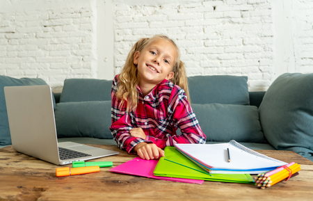 Cute caucasian cheerful elementary student feeling happy while doing homework and studying on her laptop in living room at home in new technology school education concept.