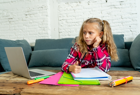 Cute elementary student feeling sad and confusing while doing difficult assignment with her laptop at home in primary school homework and children education concept.