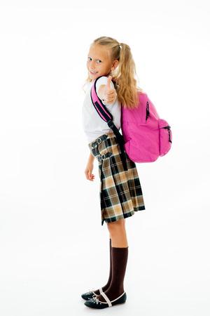 Chica de cabello rubio muy linda con una mochila rosa mirando a la cámara mostrando el pulgar hacia arriba gesto feliz de ir a la escuela aislada sobre fondo blanco en concepto de educación de regreso a la escuela y los niños.