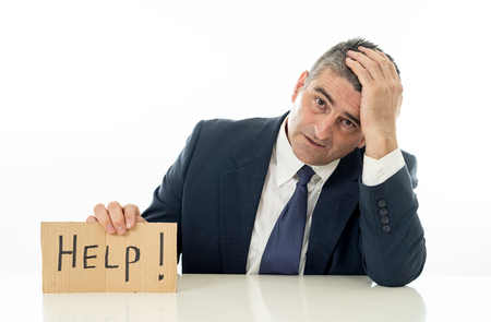 Helpless mature businessman holding a help sign in financial crisis unemployment stress and depression concept isolated in white background. Stok Fotoğraf