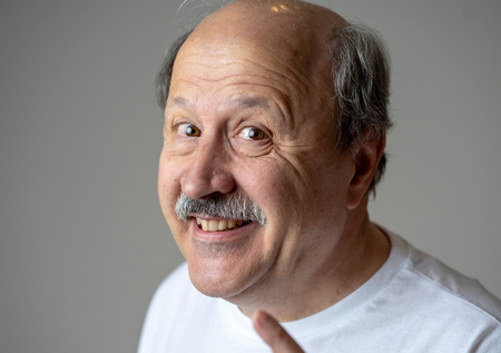 Portrait of happy and cheerful senior mature man smiling and excited gesturing funny and comic in laughter in Facial Expressions Human Emotions concept isolated on grey background. Stock Photo
