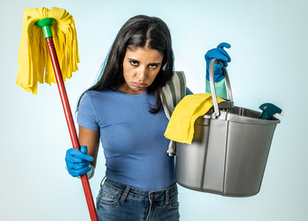 Young beautiful angry and upset housewife woman holding bucket mop cleaning spray feeling sad frustrated and lazy in domestic duties concept isolated on white background Фото со стока