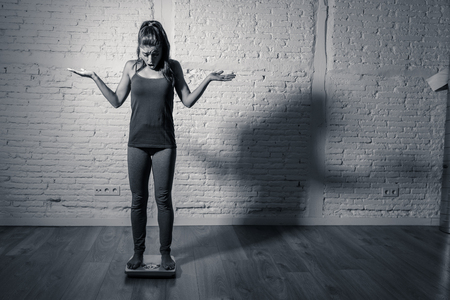 Young fit and slim woman checking body weight on scale finding herself fat and feeling depressed and desperate with big edgy shadow light in eating disorder and dieting concept. Archivio Fotografico