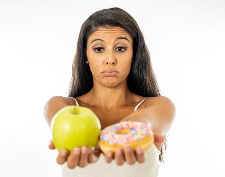 Schöne junge Frau versucht, zwischen Apfel und Donut in gesundem ungesundem Essen, Entgiftungsessen, Kalorien und Diätkonzept wählen zu müssen. Standard-Bild