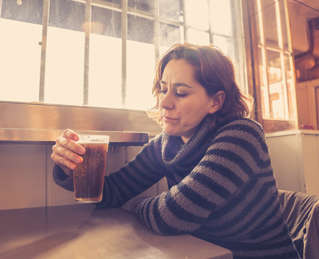 Portrait of a attractive latin woman drinking beer in a bar pub feeling depressed unhappy and lonely in Alcohol Use Abuse Depression and mental health concept. Foto de archivo
