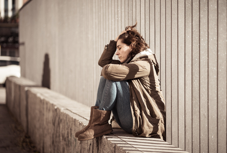 Young adult felling shame depressed and hopeless sitting alone in city urban street in Depression Loneliness Mental health Emotional pain Social violence Abusive relationship and Harassment concept.