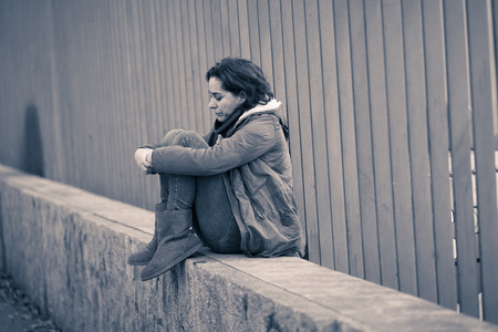 Attractive woman suffering from depression felling sad unhappy heartbroken and lonely sitting in city urban street in Mental health Emotional pain Abusive relationships and loneliness concept.