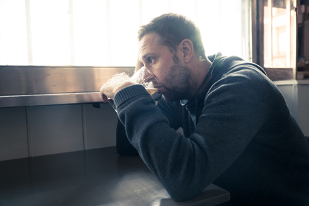 Portrait of a attractive caucasian man drinking beer in a bar pub feeling depressed unhappy and lonely in Alcohol Use Abuse Depression and mental health concept.