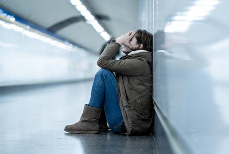 Junge Erwachsene, die Scham deprimiert und hoffnungslos sitzen, allein auf dem Untergrund der U-Bahn in Depressionen Einsamkeit Psychische Gesundheit Emotionaler Schmerz Soziale Gewalt Missbrauchsbeziehung und Belästigungskonzept.