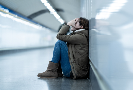 Young adult felling shame depressed and hopeless sitting alone on subway city ground in Depression Loneliness Mental health Emotional pain Social violence Abusive relationship and Harassment concept. Reklamní fotografie