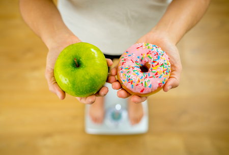 Close up of woman on scale holding on hands apple and doughnut making choice between healthy unhealthy food dessert while measuring body weight in Nutrition Health care Diet and temptation concept. Stock Photo