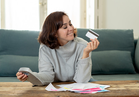 Young attractive latin business woman looking happy and satisfied with credit debit card advantages and use and accounting costs, charges, taxes and mortgage with calculator on sofa at home . Standard-Bild