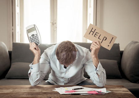 Worried and desperate business man asking for help in paying off debts and loan calculating bills tax expenses and accounting finances sitting on couch in paying bills and Financial problems concept.