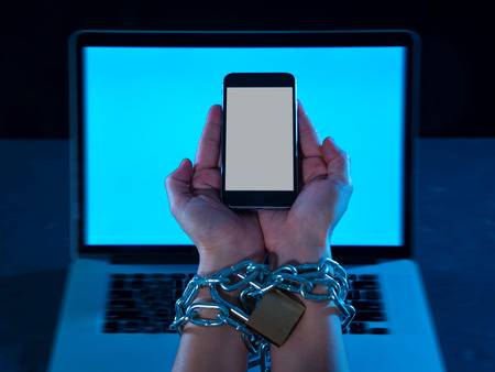 Young man addicted to mobile phone hands bond tied and locked with iron metallic chain with padlock on wrists in smart phone internet and social media addiction and slave technology victim concept. 写真素材