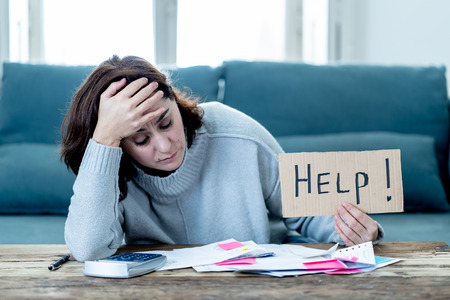 Worried and desperate woman asking for help in paying off debts and loan calculating bills tax expenses and accounting home finances sitting on couch in Domestic bills and Financial problems concept.