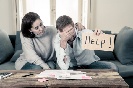Stressed young couple needing help in accounting home finance paying bills mortgage bank statements and expenses feeling desperate having so many debts in bad financial situation and bankruptcy.