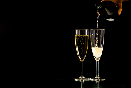 Two glasses with champagne pouring from bottle ready to toast in Celebration concept at New Years eve Christmas Valentines day and happy times isolated on black background copy space and studio light. Banco de Imagens