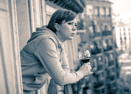 Young beautiful depressed lonely woman depressed suffering pain stress and anxiety feeling hopeless drinking looking out the street on balcony at home In depression alcohol and mental health concept. Imagens