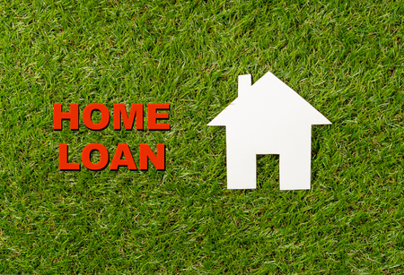 Conceptual picture of white house and text Home Loan written on green grass field top view and copy space in Property investment Real estate Saving and buying a home mortgage and loan banking concept.