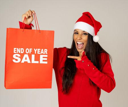 Young woman in red and santa hat excited with sale paper bags isolated grey background in ready for christmas shopping and new years sales consumerism Discounts and Christmas marketing promotions.