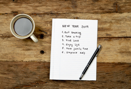 Top View 2019 New year list with resolutions and wishes for new life written on notepad coffee and pen on Vintage table background in dreams and Goals for happiness Aspiration and Motivation Concept.