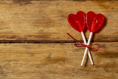 Dos lindas piruletas en forma de corazón rojo en la mesa de madera rústica y la luz del estado de ánimo romántico hermoso y desenfoque de fondo como metáfora del amor, la unión y el concepto de diseño de coche de saludos del día de San Valentín Foto de archivo