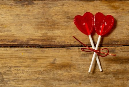 Two cute red heart shaped lollipops on rustic wooden table and beautiful romantic mood light and blur background as metaphor of love, togetherness and Valentines day greetings car design concept.