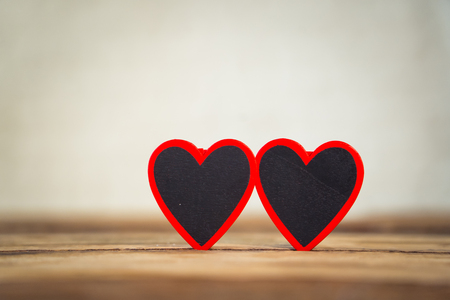 Two red hearts on vintage rustic wooden table and romantic light with background out of focus in Valentines day, love, Mothers Fathers day and Wedding Greeting card concept. Copy space for message.