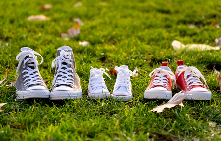 Conceptual image of family sneakers shoes in father mother and baby sizes on grass in beautiful autumn sunset light for togetherness Happy Family Expecting young parents and outdoors lifestyle. Reklamní fotografie