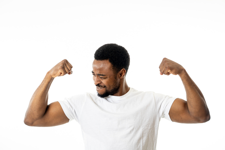 Young strong handsome african american man showing arms muscles smiling proud having fun in people, Happiness, Fitness, success Human emotions and facial expressions concept. 免版税图像