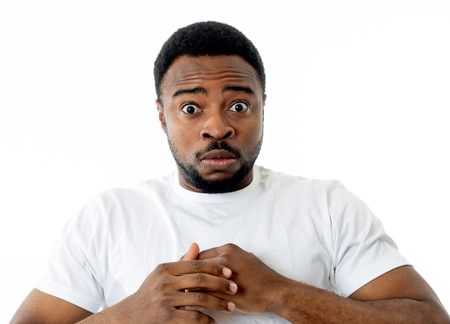 Portrait of Handsome young man in shock with a scared expression on his face making frightened and defending gestures in human emotions feelings and facial expression. Isolated on grey background. Stock Photo