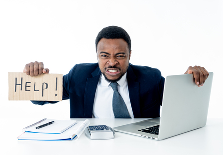 Desperate african american businessman with laptop computer suffering stress at work holding sign asking for help looking sad angry and overworked, Isolated in white. People and business concept. Stock Photo