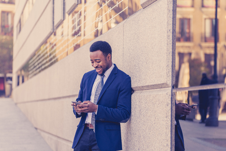 Young man in smart wear on mobile phone sending text email or social media app outdoors at city street. Happy business people, working outside, entrepreneur and work freedom communication technology.