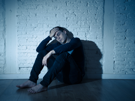 Portrait of sad depressed young man crying devastated feeling hurt suffering Depression in People, Sadness, Emotional pain, Loneliness and Heartbroken concept with copy space and dark mood light. Stock Photo