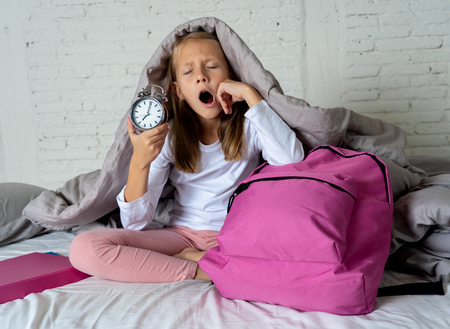 Beautiful blonde little girl sad sleepless and angry showing alarm clock time to get ready for school in difficulties waking up in the morning Children insomnia and sleeping disorders concept.