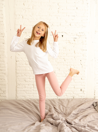 beautiful cute blonde girl feeling happy and having fun jumping and playing on bed in her bedroom at home in kids happiness healthy lifestyle and family concept.