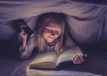 Happy smart girl reading a fairytale book lying in the dark under the cover bed holding a lantern in Reading skills Literature School Success and Education concept.
