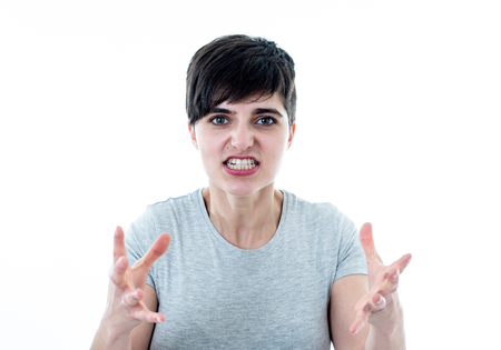 Close up portrait of Young attractive caucasian woman with an angry face. Looking mad and crazy shouting and making furious gestures. Isolated on white background. Facial expressions and emotions.
