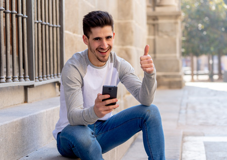 Happy student flirting and dating online and sending text message using smart phone while traveling or studying in an european city. Social network, mobile phone applications and dating sites concept