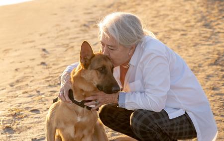 Portrait d'une belle veuve plus âgée et d'un chien de berger allemand profitant de son compagnon et de son amour sur la plage dans Avantages des animaux Mode de vie actif à la retraite et tourisme adapté aux chiens dans la lumière de l'après-midi. Banque d'images