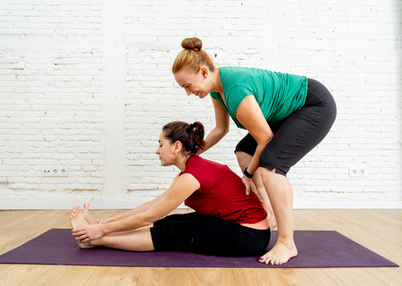 Yoga teacher and student doing yoga in Seated forward bend exercise paschimottanasana pose working out in studio home in Mindfulness Meditation Yoga benefits and Mental Emotional Physical Well being.