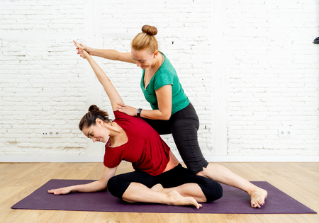 Yoga instructor Teacher helping young woman stretching with yoga pose in urban studio indoors white brick wall background in Fitness Yoga benefits Mental Emotional and Physical well-being concept.