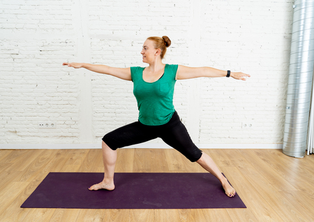 Portrait of young attractive Yoga teacher practicing standing in Warrior two exercise Virabhadrasana II pose in Fitness Working out Yoga benefits and Mental Emotional and Physical Well being concept.