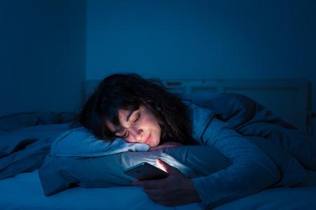 Mujer joven adicta chateando y navegando en internet usando su teléfono inteligente somnolienta, aburrida y cansada a altas horas de la noche. Luz oscura dramática. En Internet, concepto de adicción móvil e insomnio.