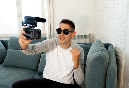 Life style portrait of young happy male blogger on camera screen filming a video tutorial for the internet. Millennial people, new fashion and modern technology, freelance and creative work concept.