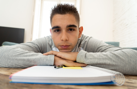 Overworked and tired university or high school male student working and studying bored and overwhelmed trying not to fall asleep. In studying for final year exam, homework an learning difficulties concept.