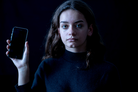 Scared upset intimidated girl bullied on mobile phone suffering the Internet dangers as gaming, viral challenges and harassment crying desperate. Child victim of cyberbullying social media effects.