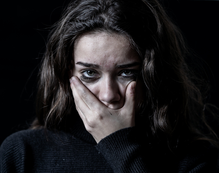 Dramatic closeup portrait of young scared, depressed girl crying alone, feeling hopeless suffering from harassment or domestic violence. Stop child abuse and neglect. Social campaign concept.
