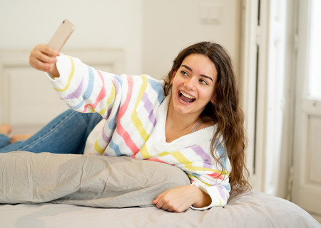 Excited trendy young teenager woman taking a selfie on smart mobile phone on bed at home. Happy talking and posting online in social media apps. In new technology, connection and Internet concept. Stock Photo
