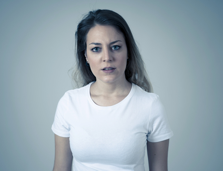 Close up ritratto di giovane donna caucasica attraente con una faccia arrabbiata. Sembrando matto e pazzo gridando e facendo gesti furiosi. Isolato su sfondo neutro. Espressioni facciali ed emozioni. Archivio Fotografico